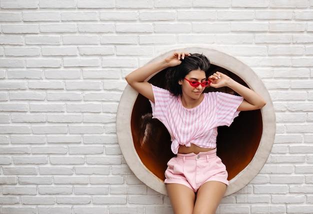 Buiten schot van geïnspireerde vrouw in zonnebril. brunette vrouw in zomerkleren poseren op stedelijke achtergrond. Gratis Foto