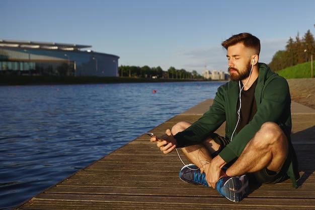 Buiten schot van knappe ongeschoren jonge kerel met stoppels doorbrengen rustige zomerochtend alleen aan het meer, zittend met de ogen dicht, luisteren naar meditatieve muzieknummers op moderne slimme telefoon Gratis Foto