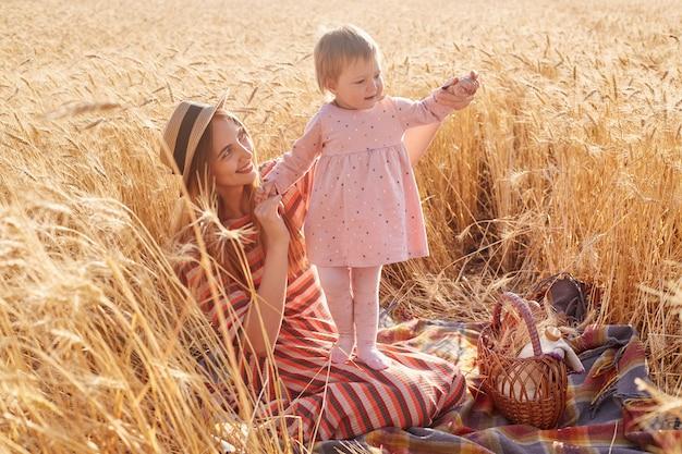 Buiten schot van mooie vrouw met haar dochtertje peuter dragen roze jurk en panty in tarweveld op zomerdag, mama gekleed gestreepte jurk en strooien hoed poseren omringd met aartjes. Premium Foto