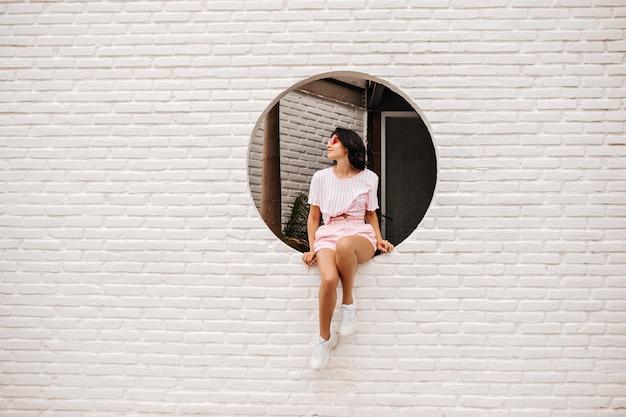 Buiten schot van peinzende vrouw in casual kleding. vrij gelooide jonge vrouw in sneakers zittend op dichtgemetseld muur. Gratis Foto