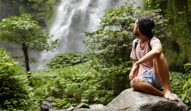 Buiten schot van stijlvolle jonge blanke wandelaar zitten blootsvoets op grote rots en kijken over zijn schouder naar prachtige waterval Gratis Foto
