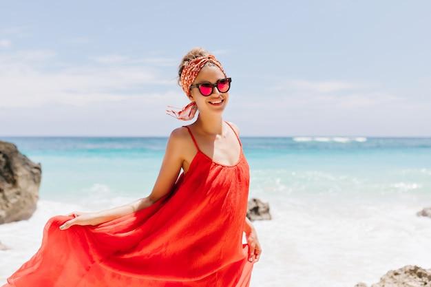 Buiten schot van verfijnd gebruind meisje poseren met plezier op het strand. portret van prachtige jonge dame spelen met rode jurk en lachend op het strand. Gratis Foto