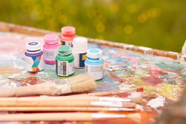 Buiten schot van verschillende containers voor verf en professionele penselen gelegen op vuile palet Gratis Foto