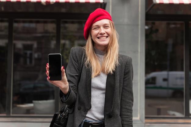 Buiten schot van vrolijke jonge mooie blonde langharige dame in rode baret scherm van haar telefoon tonen en gelukkig kijken met een brede glimlach, staande over café buitenkant Gratis Foto