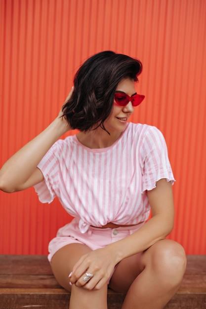 Buiten schot van vrouw in roze gestreepte t-shirt. brunette vrouw in zonnebril poseren op houten bank. Gratis Foto