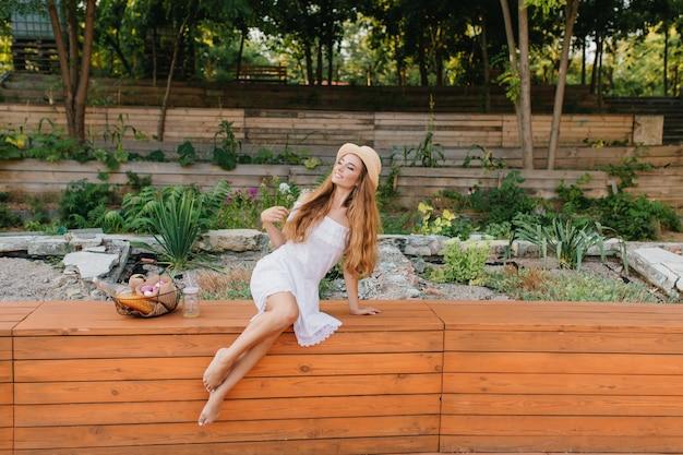 Buiten van dromerige blootsvoets dame met lang krullend haar zittend op een houten bankje in het park en wegkijken. romantisch meisje in strooien hoed en witte jurk poseren voor bloembed. Gratis Foto