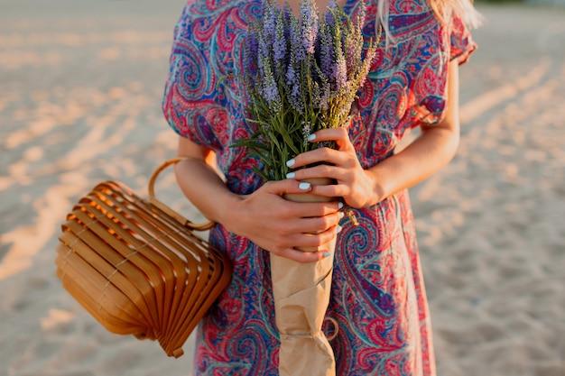 Buiten zomer beeld van mooie romantische blonde vrouw in kleurrijke jurk wandelen op het strand met boeket lavendel. Gratis Foto