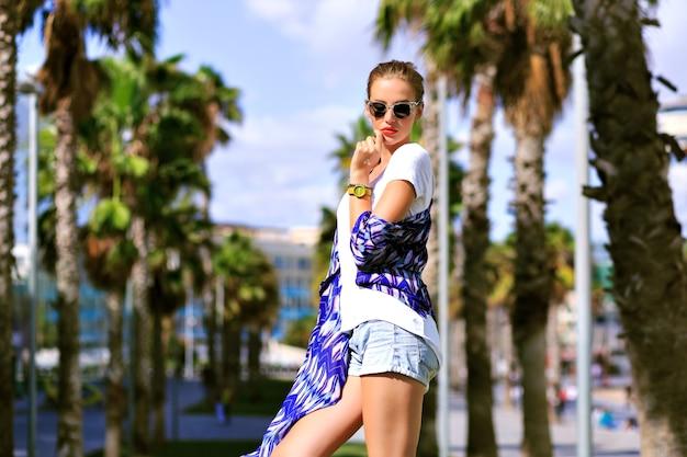 Buiten zomer mode portret van stijlvolle vrouw poseren in de buurt van palmbomen, genieten van exotische vakantie, casual outfit, laarzen en zonnebrillen, felle kleuren, reizen in barcelona, felle kleuren, straatstijl. Gratis Foto