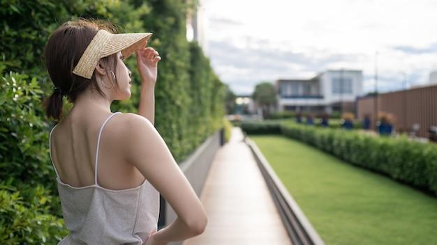 Buiten zomer portret achteraanzicht van vrouw met strooien hoed op weg en groene tuin Premium Foto