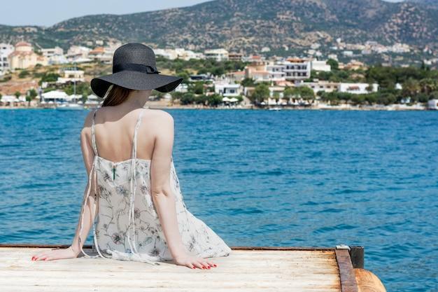 Buiten zomer portret van jonge mooie vrouw kijken naar de zee in de haven van agios nikolaos, geniet van haar vrijheid en frisse lucht, gekleed in stijlvolle hoed en kleding. Premium Foto
