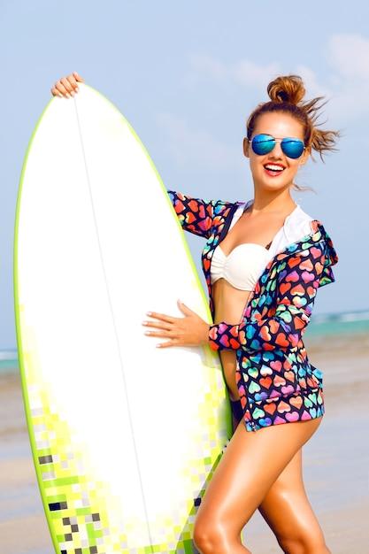 Buiten zomer portret van lachende vrouw met surfer board in de buurt van blauwe oceaan Gratis Foto
