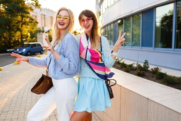 Buiten zonnige levensstijl portret van gelukkige verlaten paar elegante meisjes samen plezier hebben op straat, stijlvolle vintage outfits, pastel truien en zonnebrillen, bijpassende accessoires, familie tijd. Gratis Foto