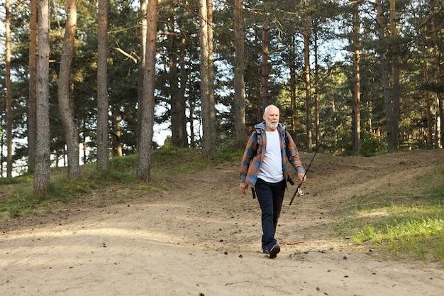 Buitenfoto van trieste oudere bebaarde man met hengel die langs het pad in het bos gaat, met een teleurgestelde gezichtsuitdrukking omdat hij helemaal geen vis ving. op visstek activiteit en recreatie Gratis Foto