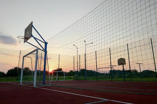 Buitenshuis mini-voetbal en basketbalveld met bal poort en mand omgeven door hoge beschermende omheining. Premium Foto