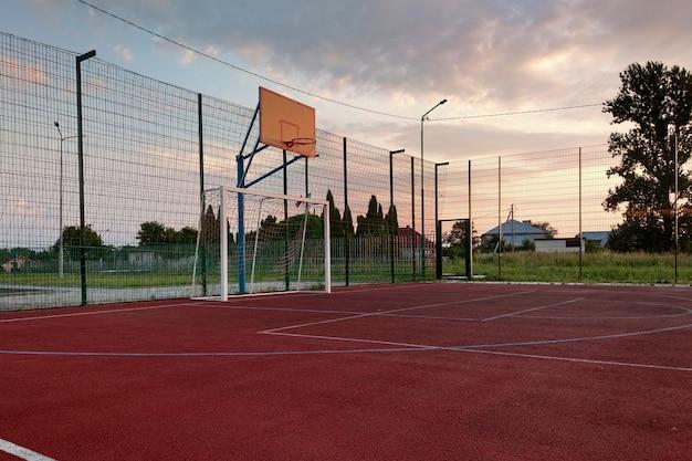 Buitenshuis minivoetbal en basketbalveld met ballenhek en basket omgeven met hoge beschermende omheining. Premium Foto