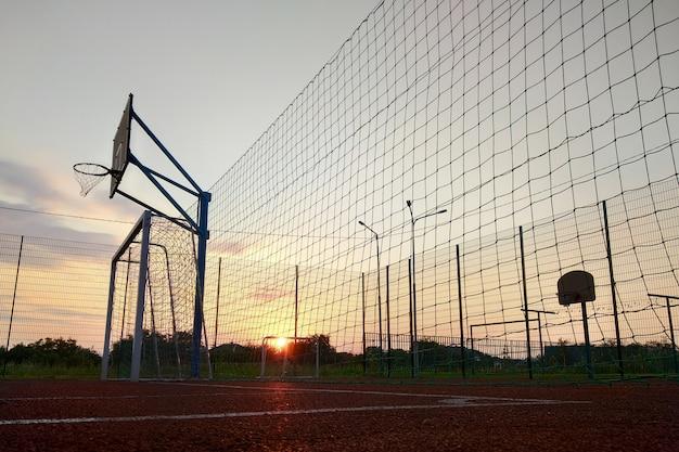 Buitenshuis minivoetbal en basketbalveld met ballenhek en basket omgeven met hoog beschermend hek. Premium Foto