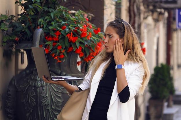 Buitensporige vrouw in modieuze kleding die in haar laptop kijkt en zich zorgen maakt over wat nieuws. legt haar hand op de wang. kijk om de pols, tas hangt aan de schouder. staande door rode bloemen Gratis Foto
