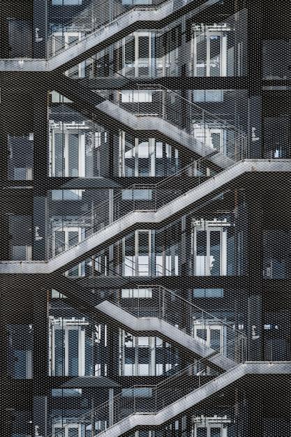 Buitentrap van een stedelijk gebouw bedekt met een metalen roosteromheining Premium Foto