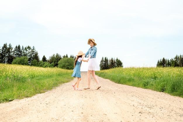 Buitenwandeling. zomer in het veld. moeder overgeven en spinsdaughter op handen op de natuur, zomerdag vakantie. Premium Foto