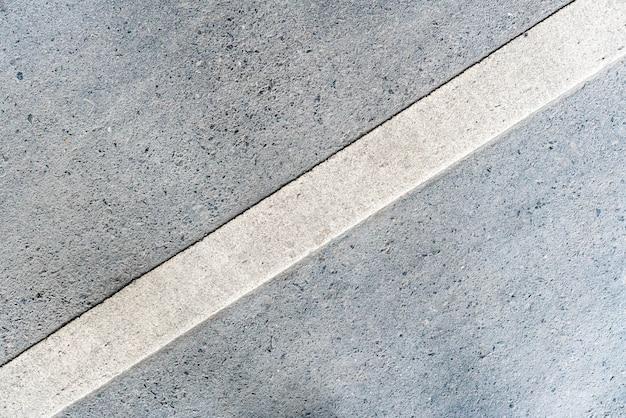 Buitenweg met 45 graden geroteerde witte lijnmarkering op de onderste textuur. Premium Foto