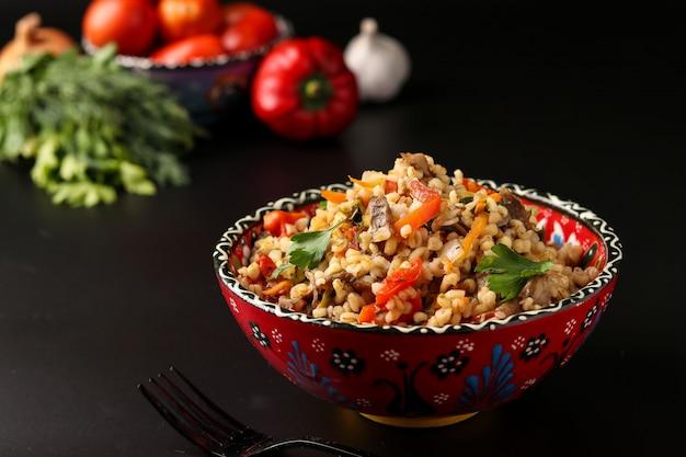 Bulgur met champignons en groenten in een kom op een donkere, vegetarische oosterse schotel, Premium Foto