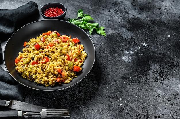 Bulgur met groenten, uien, paprika, wortelen en peterselie in een bord. zwarte achtergrond Premium Foto
