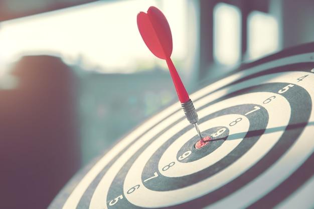 Bulls eye of dartbord heeft een rode pijlworp die het midden van een schietend doel raakt. Premium Foto