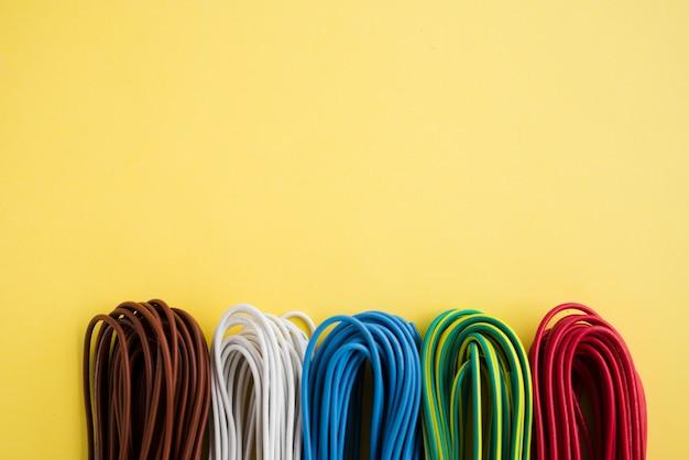 Bundel van kleurrijke elektronische draad over duidelijke gele achtergrond Gratis Foto