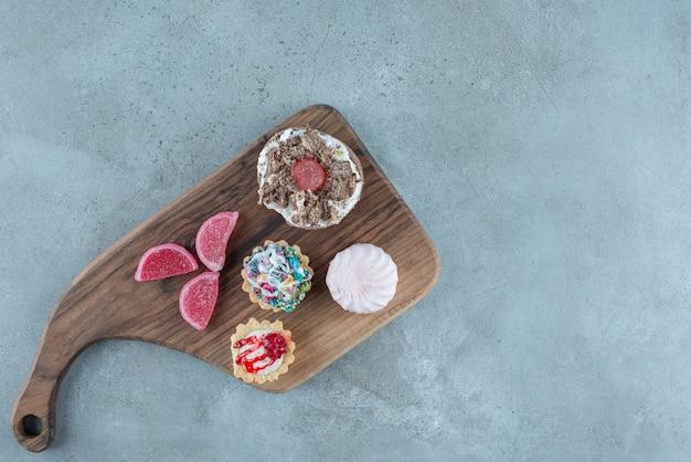 Bundel van verschillende gebakjes en marmelades op een houten bord op marmeren achtergrond. hoge kwaliteit foto Gratis Foto