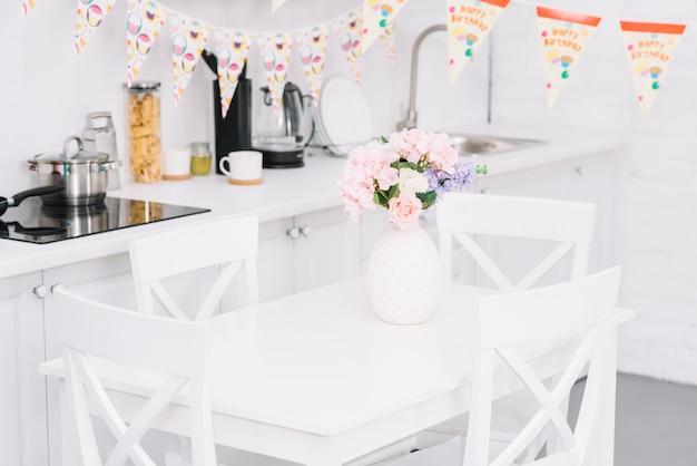 Bunting over lijst met mooie bloemvaas in moderne keuken Gratis Foto