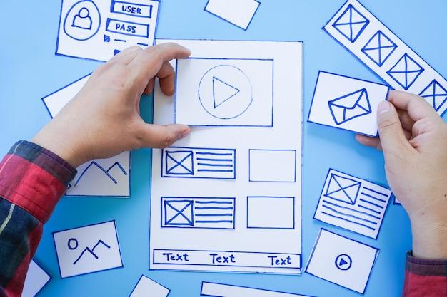 Bureau met handsortering van wireframe-schermen van een mobiele responsieve website. Premium Foto