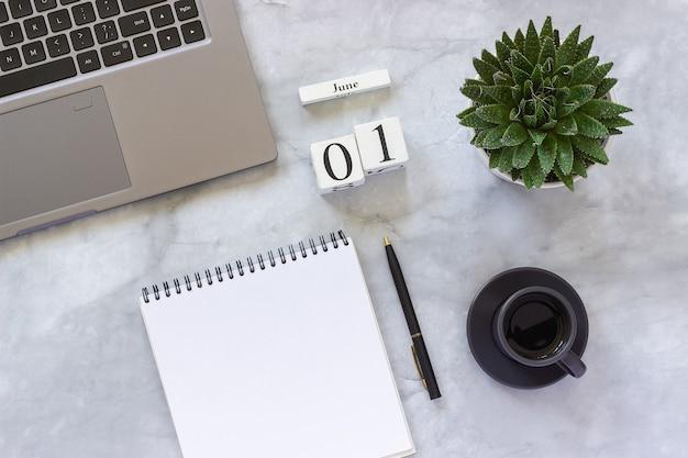 Bureau of thuis tafel bureau. houten kubussen kalender 1 juni. grijze laptop, kladblok, kopje koffie, sappig op marmeren achtergrond Premium Foto