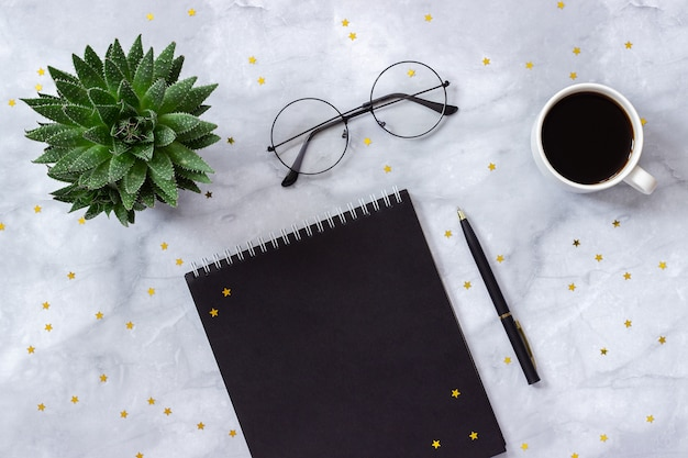 Bureau of thuis tafel. zwarte blocnote, pen, kop van koffie, succulent op marmeren achtergrond Premium Foto