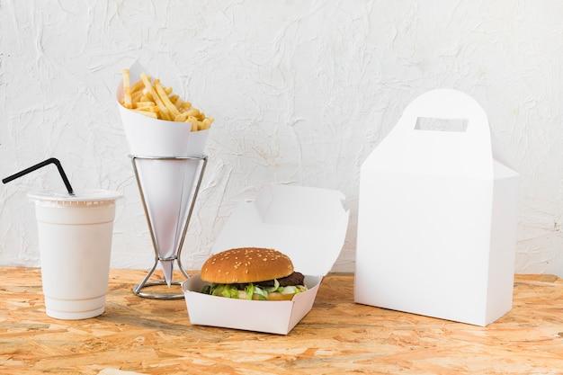 Burger; franse frietjes; beker en voedselpakket mock up op houten tafelblad Gratis Foto