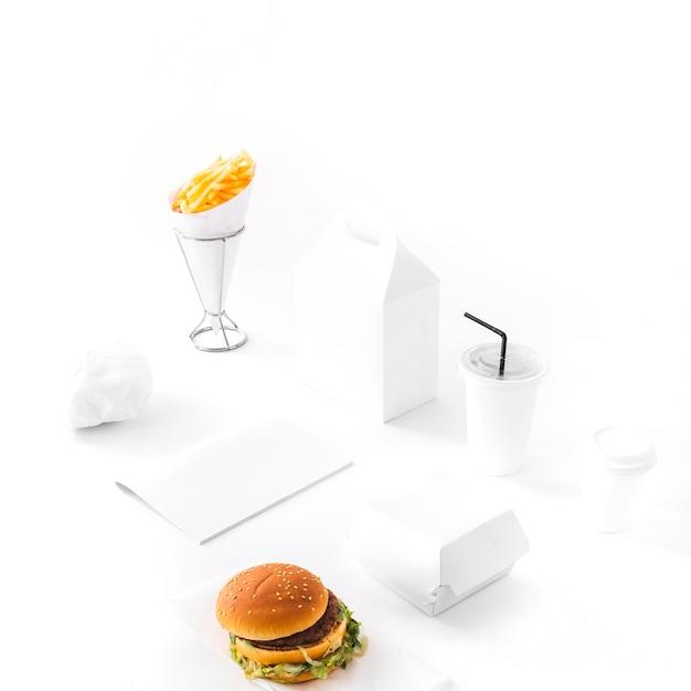 Burger; franse frietjes; besteedbaar drank en document pakket op witte achtergrond Gratis Foto