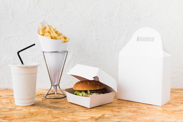 Burger; frieten en verwijdering cup op houten tafel Gratis Foto