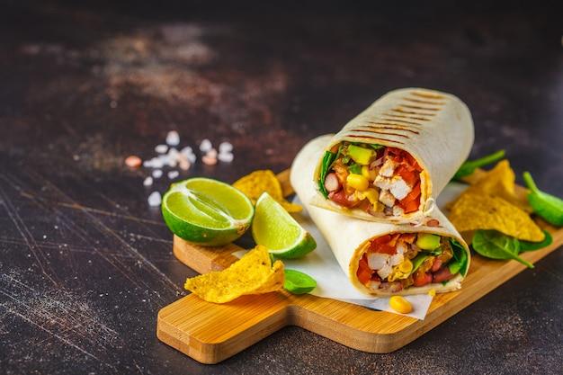Burrito's wraps met kip, bonen, maïs, tomaten en avocado op een houten bord Premium Foto