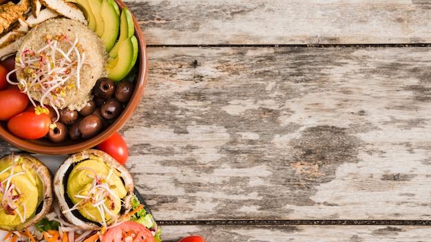 Burritokom met kip; tomaat; spruiten; olijven en avocado plakjes in kom met salade op houten gestructureerde achtergrond Gratis Foto