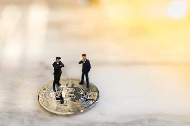 Business, e-commerce, crypto-valuta, financiën en technologie. sluit omhoog van twee zakenman miniatuurcijfer zich bevindt op bitcoinmuntstuk op grond met copyspace. Premium Foto