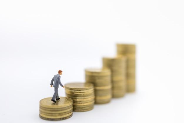 Business, geld, financiën en management concept. sluit omhoog van zakenman miniatuurcijfer die bovenop stapel gouden muntstukken lopen. Premium Foto