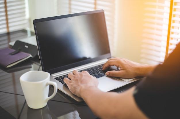 Business man aan het werk op laptop, jonge man maakt gebruik van technologie Premium Foto