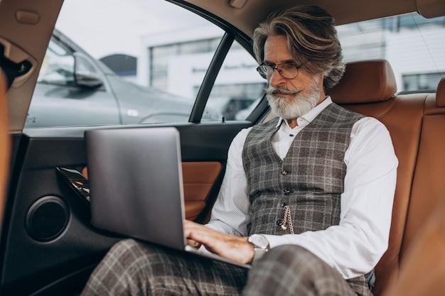 Business man zit in zijn auto aan de achterkant zitten Gratis Foto