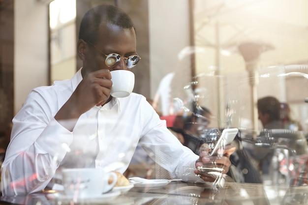 Business, moderne technologie, communicatie en mensen concept. vertrouwen stijlvolle afro-amerikaanse zakenman in ronde zonnebril cappccino drinken in de coffeeshop, zittend door raam met mobiele telefoon Gratis Foto