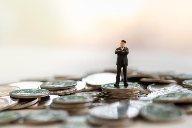 Business, planning, beveiliging, pensioen en sparen concept. sluit omhoog van zakenman miniatuurcijfer die bovenop stapel muntstukken met exemplaarruimte lopen. Premium Foto