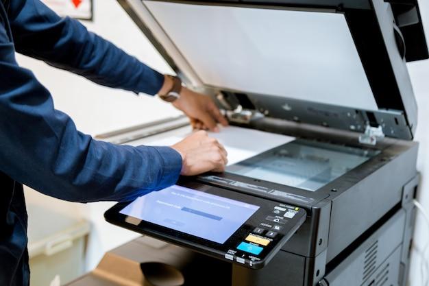 Bussiness-man handdrukknop op paneel van printer Premium Foto