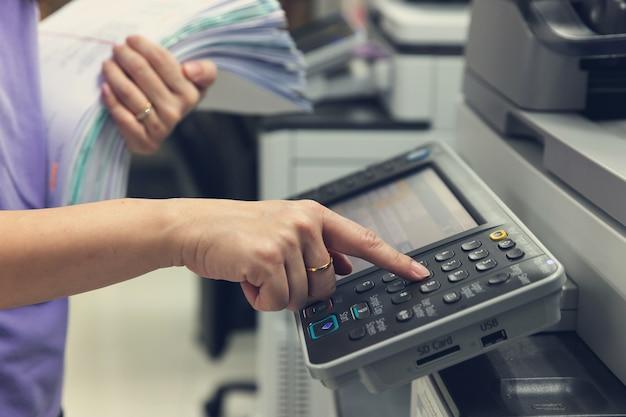 Bussinesswoman die kopieerapparaatmachine gebruiken om administratie te kopiëren. Premium Foto