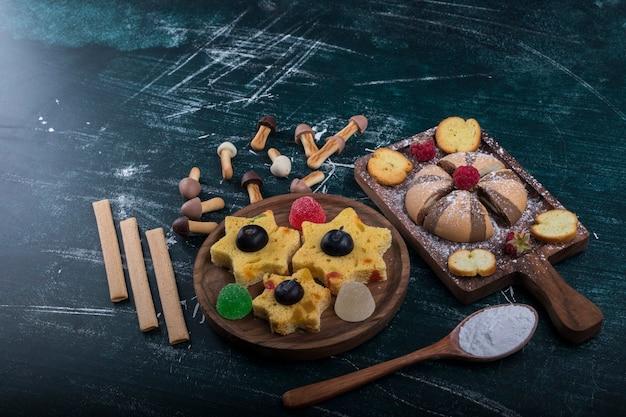 Cacao en vanille koekjes op een houten bord met koekjes in stervorm opzij Gratis Foto