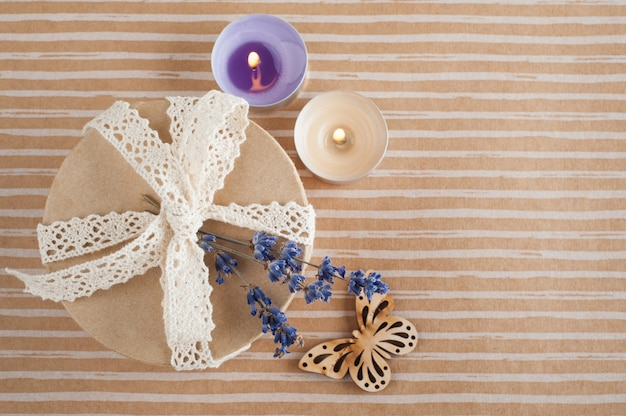 Cadeau met kanten strik, lavendel, verlichte kaars Premium Foto
