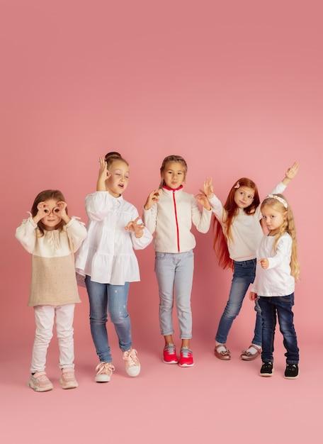 Cadeautjes geven en krijgen tijdens kerstvakantie. groep gelukkige glimlachende kinderen die pret hebben, vieren geïsoleerd op roze studioachtergrond. nieuwjaar 2021 ontmoeting, jeugd, geluk, emoties. Gratis Foto