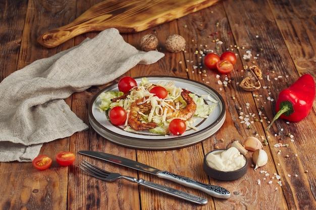 Caesar salade met garnalen in een witte plaat op houten tafel Premium Foto